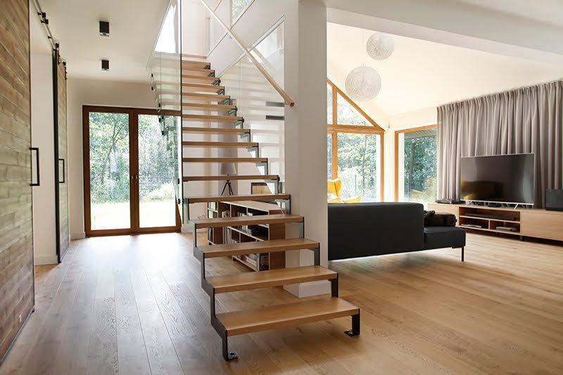 duże drzwi przesuwne, drzwi przesuwne w rezydencji, jak oddzielić salon od części prywatnej, nowoczesny salon, podwójne drzwi przesuwne, drzwi przesuwne dwuskrzydłowe, drzwi drewniane w metalowej ramie, otwarta przestrzeń, aranżacja przestrzeni w salonie, duże okna w salonie, ażurowe schody drewniane