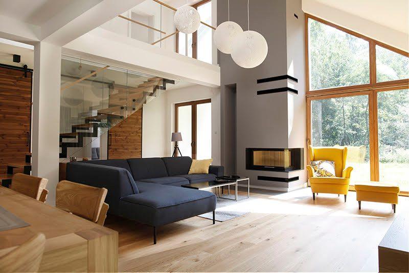 duże drzwi przesuwne, drzwi przesuwne w rezydencji, jak oddzielić salon od części prywatnej, nowoczesny salon, podwójne drzwi przesuwne, drzwi przesuwne dwuskrzydłowe, drzwi drewniane w metalowej ramie, niebieska sofa, kanapa w stylu skandynawskim, stalowe dodatki we wnętrzu, otwarta przestrzeń, żółty fotel w salonie, aranżacja saloun z kominkiem, duże wiszące lampy