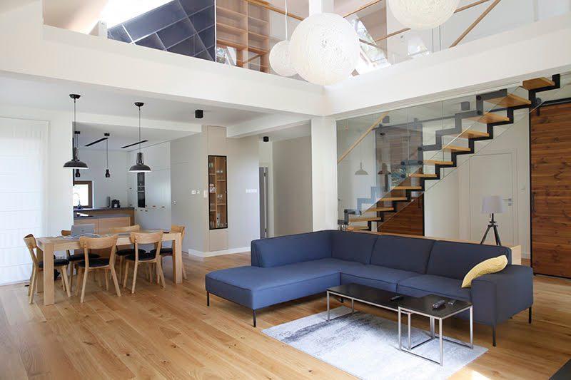 duże drzwi przesuwne, drzwi przesuwne w rezydencji, jak oddzielić salon od części prywatnej, nowoczesny salon, podwójne drzwi przesuwne, drzwi przesuwne dwuskrzydłowe, drzwi drewniane w metalowej ramie, niebieska sofa, kanapa w stylu skandynawskim, stalowe dodatki we wnętrzu, otwarta przestrzeń