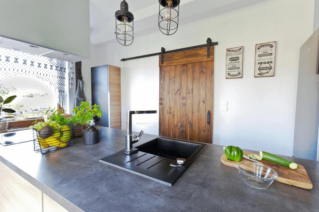 drzwi przesuwne w kuchni, drzwi przesuwne szczotkowane, drzwi przesuwne drewniane, drzwi przesuwne w stylu barn door, szara kuchnia, kuchnia rustykalna, industrialna lampa wisząca