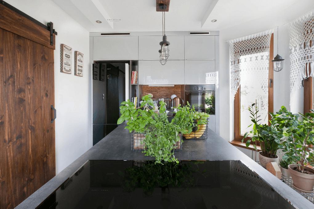 drzwi przesuwne w kuchni, drzwi przesuwne szczotkowane, drzwi przesuwne drewniane, drzwi przesuwne w stylu barn door, szara kuchnia, kuchnia rustykalna, kwiaty w kuchni, rustykalne dodatki w kuchni