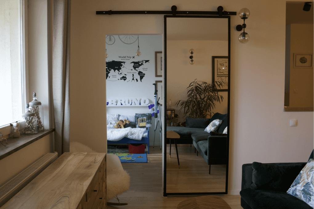 drzwi przesuwne z lustrem, drzwi z lustrem w metalowej ramie, drzwi przesuwne w nowoczesnym wnętrzu, kanapa w stylu skandynawskim, zielona sofa, lampy ścienne metalowe