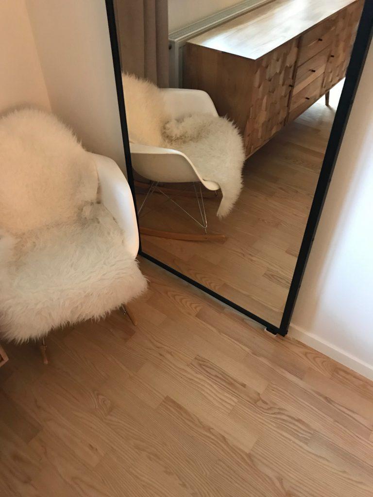 drzwi przesuwne z lustrem, drzwi z lustrem w metalowej ramie, drzwi przesuwne w nowoczesnym wnętrzu, komoda w stylu modern retro, biały fotel bujany, lustro w salonie