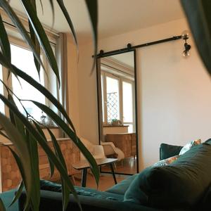 drzwi przesuwne z lustrem, drzwi z lustrem w metalowej ramie, drzwi przesuwne w nowoczesnym wnętrzu, zielona sofa, duże lustro w salonie