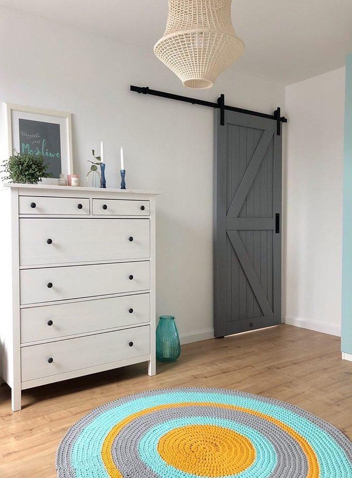 drzwi przesuwne do sypialni, drzwi przesuwne szare, drzwi drewniane, drzwi szare, wnętrze z miętowymi dodatkami, miętowo-szare wnętrze, biała komoda w salonie, dywanik w salonie, pastelowe wnętrze