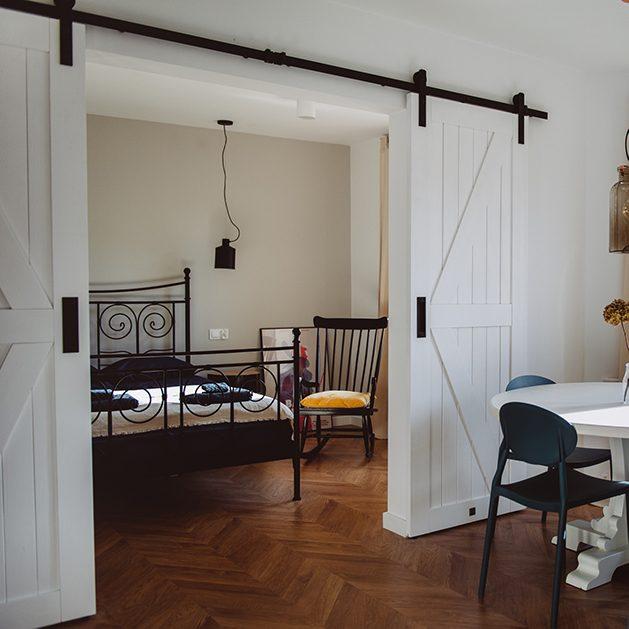 styl modern retro, apartamenty do wynajęcia Wrocław, drzwi przesuwne dwuskrzydłowe, drzwi przesuwne podwójne, drzwi przesuwne białe, drzwi przesuwne barn door, otwarta przestrzeń, podwójne drzwi do sypialni, łóżko do sypialni w stylu retro, fotel bujany w sypialni
