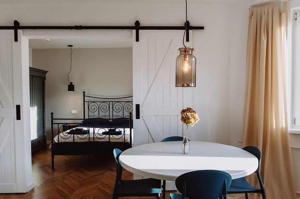 styl modern retro, apartamenty do wynajęcia Wrocław, drzwi przesuwne dwuskrzydłowe, drzwi przesuwne podwójne, drzwi przesuwne białe, drzwi przesuwne barn door, otwarta przestrzeń, podwójne drzwi do sypialni, łóżko do sypialni w stylu retro, lampa wisząca rustykalna