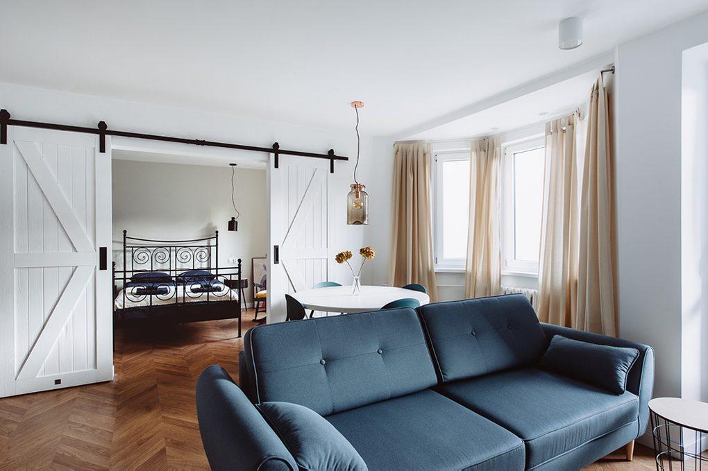 styl modern retro, apartamenty do wynajęcia Wrocław, drzwi przesuwne dwuskrzydłowe, drzwi przesuwne podwójne, drzwi przesuwne białe, drzwi przesuwne barn door, otwarta przestrzeń, podwójne drzwi do sypialni, łóżko do sypialni w stylu retro