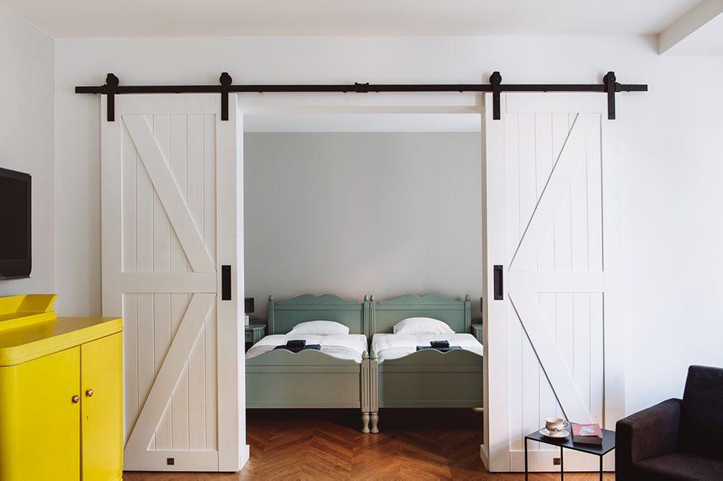 styl modern retro, apartamenty do wynajęcia Wrocław, drzwi przesuwne dwuskrzydłowe, drzwi przesuwne podwójne, drzwi przesuwne białe, drzwi przesuwne barn door, żółta komoda w salonie, podwójne drzwi do sypialni, podwójne łóżko w sypialni