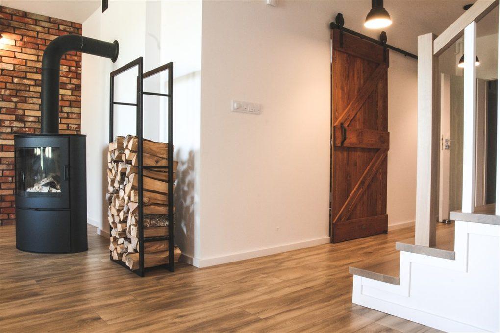 """wnętrze w stylu skandynawskim, wnętrze w stylu loftowym, drzwi do kuchni, drzwi drewniane w stylu """"barn door"""", drzwi przesuwne szczotkowane, drzwi przesuwne barn door, drzwi przesuwne do kuchni, cegła na ścianie w salonie, otwarta przestrzeń, kominek w salonie"""