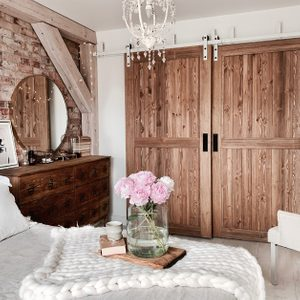 """drzwi przesuwne drewniane, drzwi przesuwne naprzemienne, styl rustykalny we wnętrzach, styl modern rustic, drzwi w stylu """"barn door"""", biały system przesuwny, system przesuwny do drzwi naprzemiennych, cegła na ścianie w sypialni, belki stropowe w sypialni, biały żyrandol rustykalny, rustykalna komoda do sypialni"""