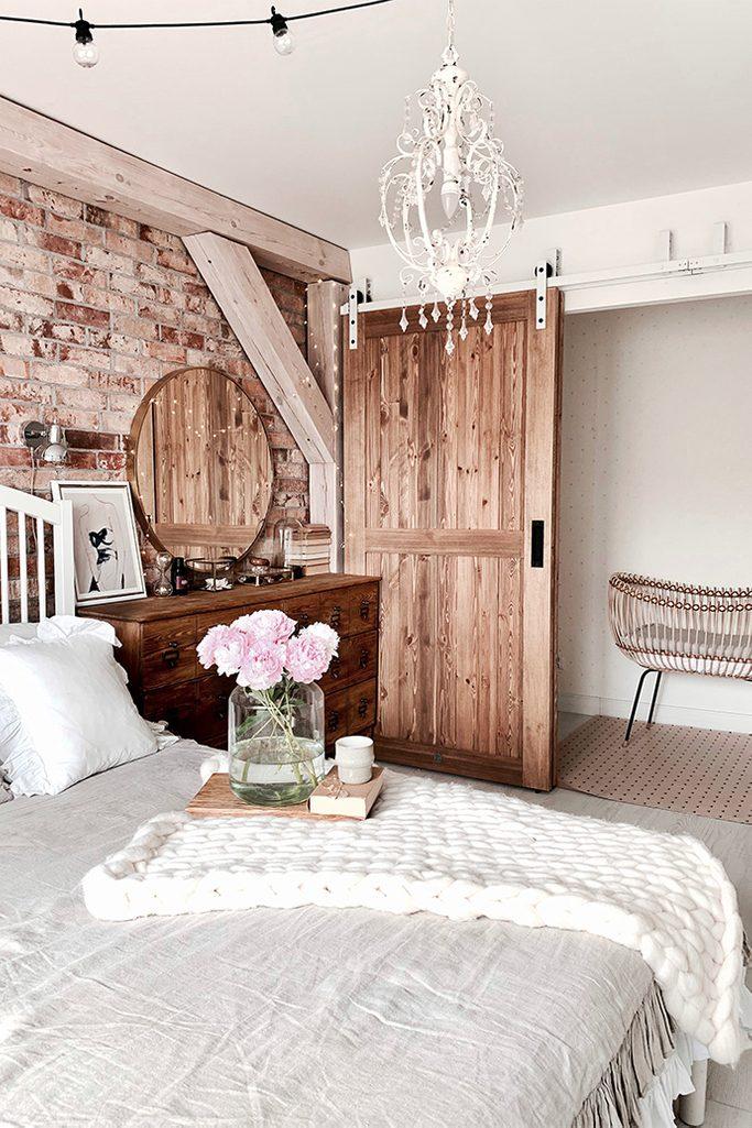 """drzwi przesuwne drewniane, drzwi przesuwne naprzemienne, styl rustykalny we wnętrzach, styl modern rustic, drzwi w stylu """"barn door"""", biały system przesuwny, system przesuwny do drzwi naprzemiennych, cegła na ścianie w sypialnii, belki stropowe w sypialni, biały żyrandol rustykalny"""