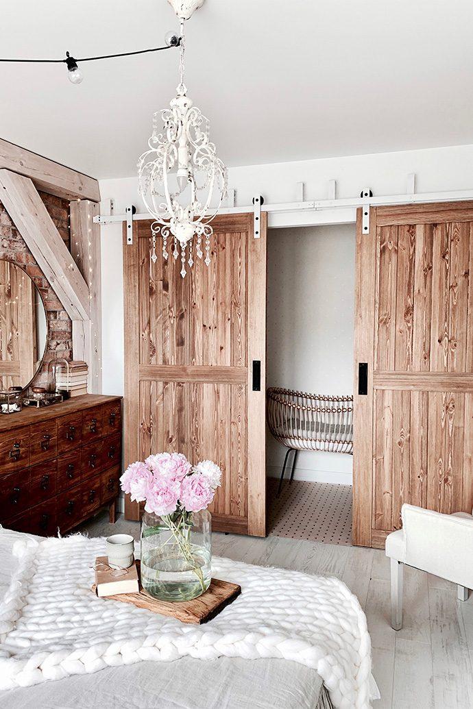 """drzwi przesuwne drewniane, drzwi przesuwne naprzemienne, styl rustykalny we wnętrzach, styl modern rustic, drzwi w stylu """"barn door"""", biały system przesuwny, system przesuwny do drzwi naprzemiennych, biały rustykalny żyrandol, cegła na ścianie w sypialni"""