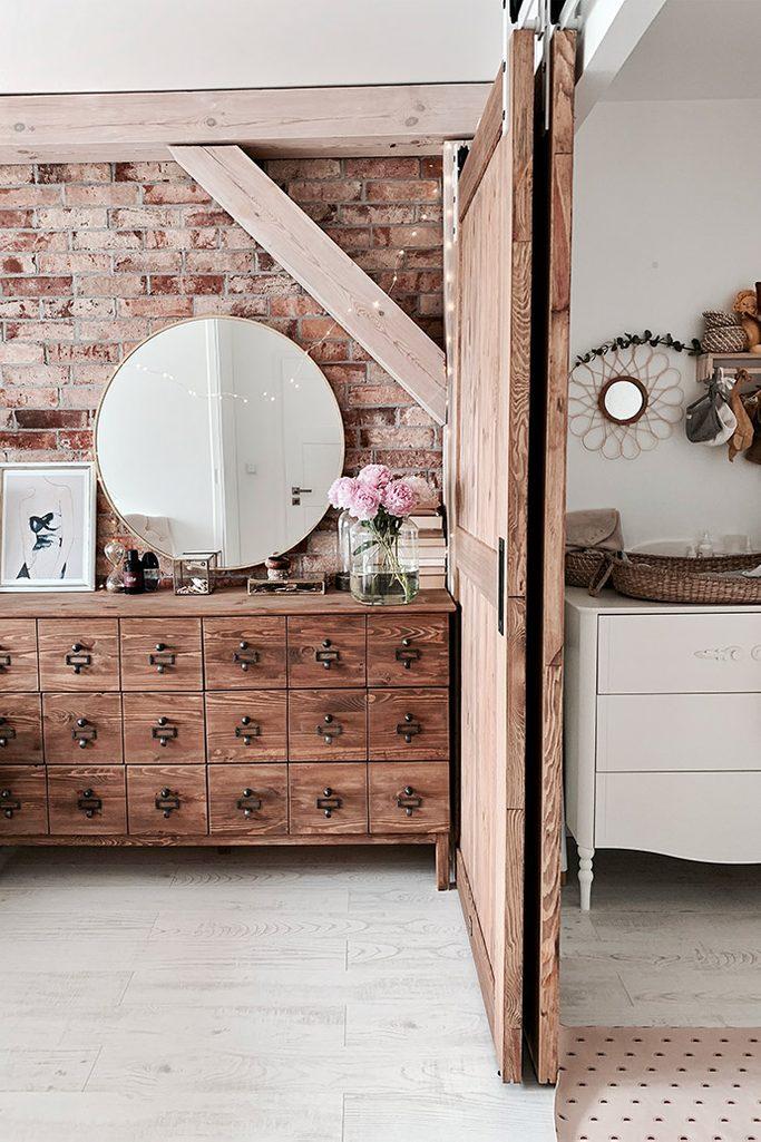drzwi przesuwne drewniane, drzwi przesuwne naprzemienne, styl rustykalny we wnętrzach, styl modern rustic, rustykalna komoda do sypialni, cegła na ścianie w sypialni, belki stropowe w sypialni
