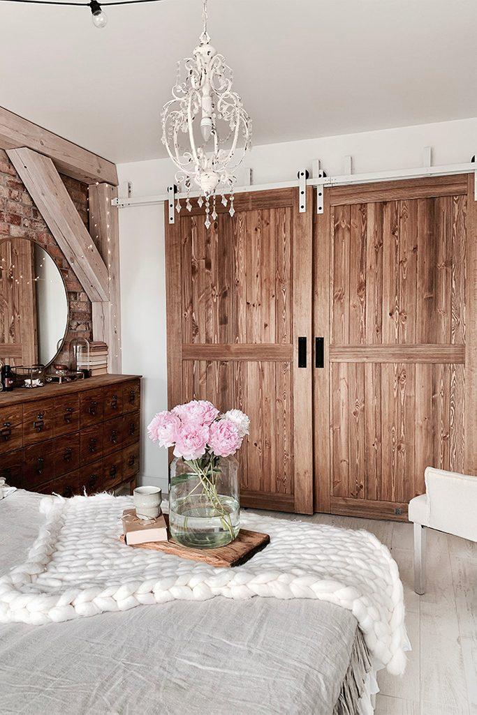 """drzwi przesuwne drewniane, drzwi przesuwne naprzemienne, styl rustykalny we wnętrzach, styl modern rustic, drzwi w stylu """"barn door"""", biały system przesuwny, system przesuwny do drzwi naprzemiennych, cegła na ścianie w sypialni, biały rustykalny żyrandol"""
