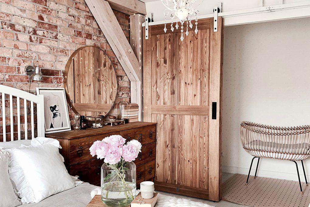 """drzwi przesuwne drewniane, drzwi przesuwne naprzemienne, styl rustykalny we wnętrzach, styl modern rustic, drzwi w stylu """"barn door"""", biały system przesuwny, system przesuwny do drzwi naprzemiennych, cegła na ścianie w sypialni,, rustykalna komoda w sypialni,"""