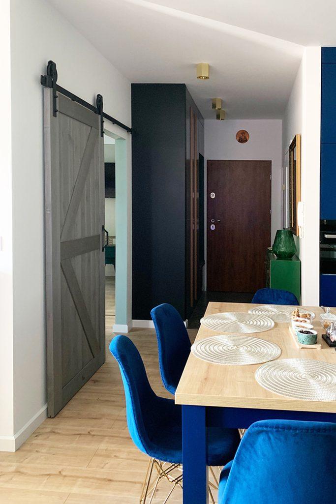 drzwi przesuwne drewniane, drzwi przesuwne w stylu barn door, drzwi przesuwne szare, złote dodatki we wnętrzu, nowoczesne wnętrze, otwarta przestrzeń, kuchnia z jadalnią i salonem, niebieskie krzesła do jadalni, drzwi przesuwne do sypialni, wyraźne kolory we wnętrzu, złote dodatki we wnętrzu