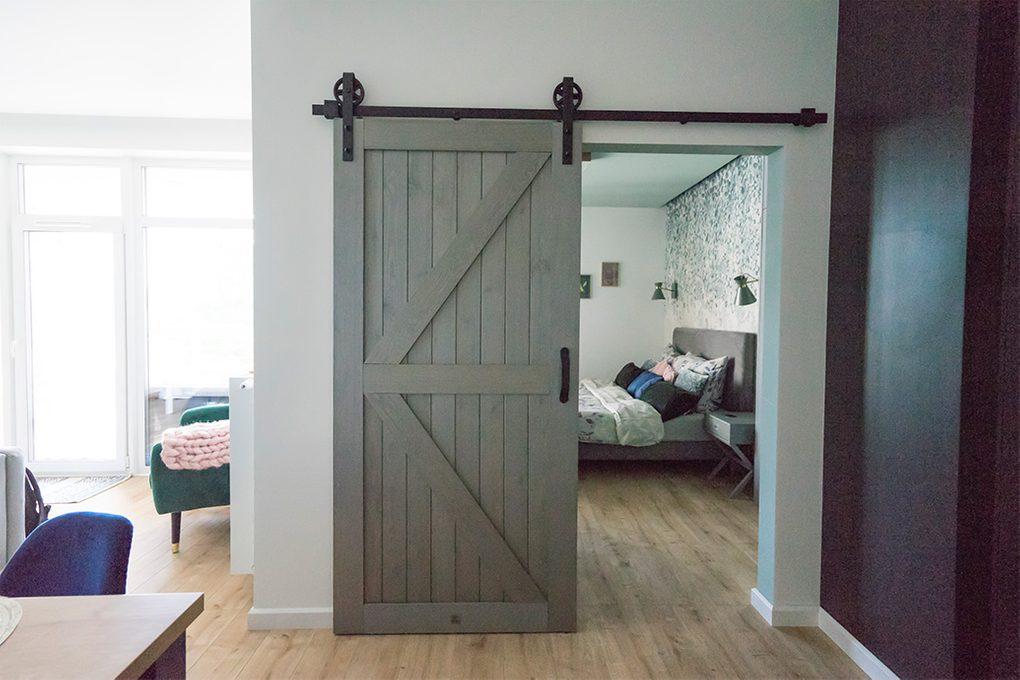 drzwi przesuwne drewniane, drzwi przesuwne w stylu barn door, drzwi przesuwne szare, klamka do drzwi przesuwnych, drzwi przesuwne do sypialni, wejście do sypialni, sypialnia w stylu modern, sypialnia w odcieniach szrości, tapeta dekoracyjna do sypialni, wyraźne kolory
