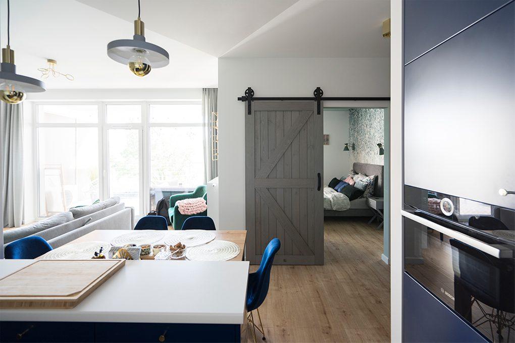 drzwi przesuwne drewniane, drzwi przesuwne w stylu barn door, drzwi przesuwne szare, złote dodatki we wnętrzu, nowoczesne wnętrze, przejście między salonem a sypialnią, wejście do sypialni, wyraźne kolory we wnętrzu, niebieskie krzesła do jadalni, otwarta przestrzeń