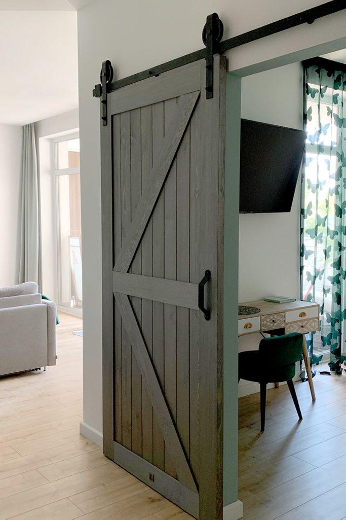 drzwi przesuwne drewniane, drzwi przesuwne w stylu barn door, drzwi przesuwne szare, złote dodatki we wnętrzu, nowoczesne wnętrze, drzwi przesuwne do sypialni,