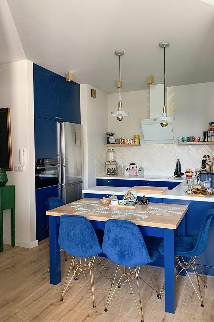 kuchnia w stylu nowoczesnym, niebieskie meble do kuchni, złote dodatki w kuchni, niebieskie krzesła w jadalni, lampy wiszące do kuchni