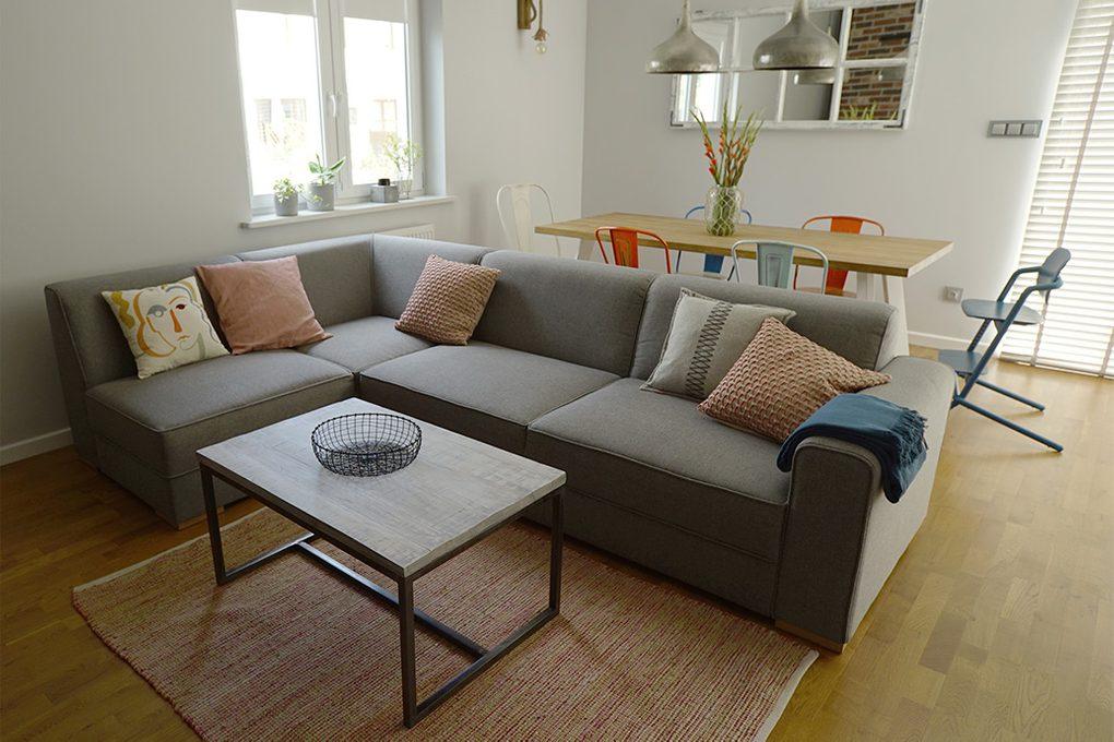 szara sofa w salonie, kącik jadalny w salonie, kolorowe krzesła do jadalni