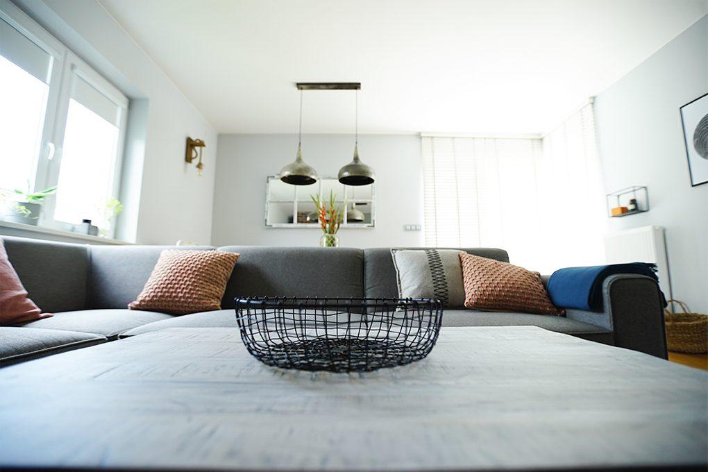 szara sofa w salonie, wiszące lampy metalowe,