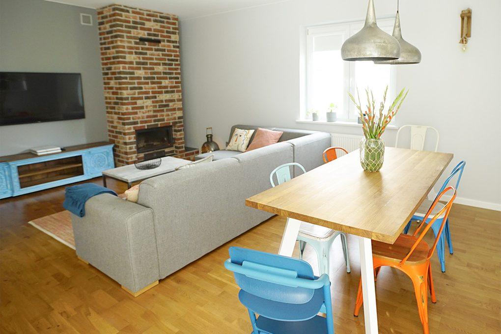 aranżacja salonu, ceglany kominek w salonie, szara sofa w salonie, kolorowe dodatki, kącik jadalny w salonie