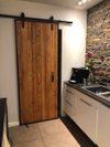 loftowe drzwi przesuwne w kuchni, drzwi w stylu loft, drewniane drzwi w metalowej ramie, cegła na ścianie w kuchni
