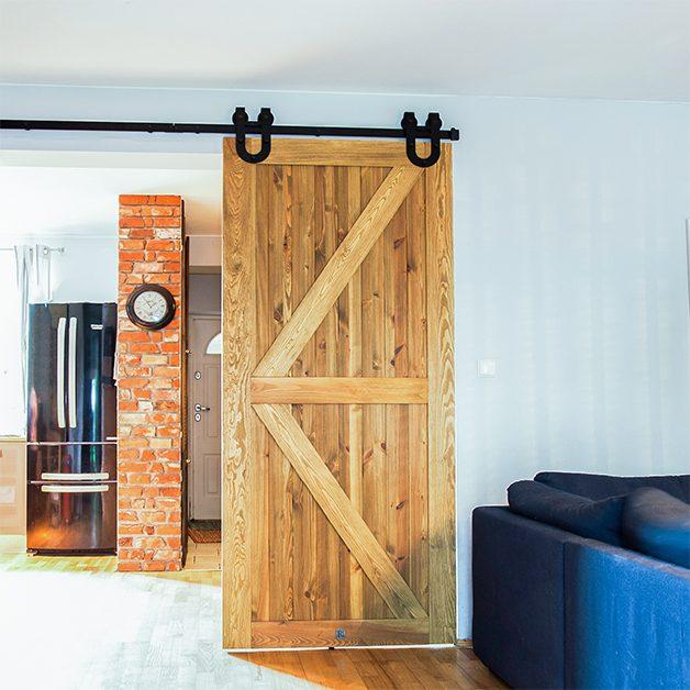 między kuchnią a salonem, drzwi przesuwne barn door, drzwi przesuwne z podkową, drzwi drewaniane rustykalne, cegła na ścianie w kuchni