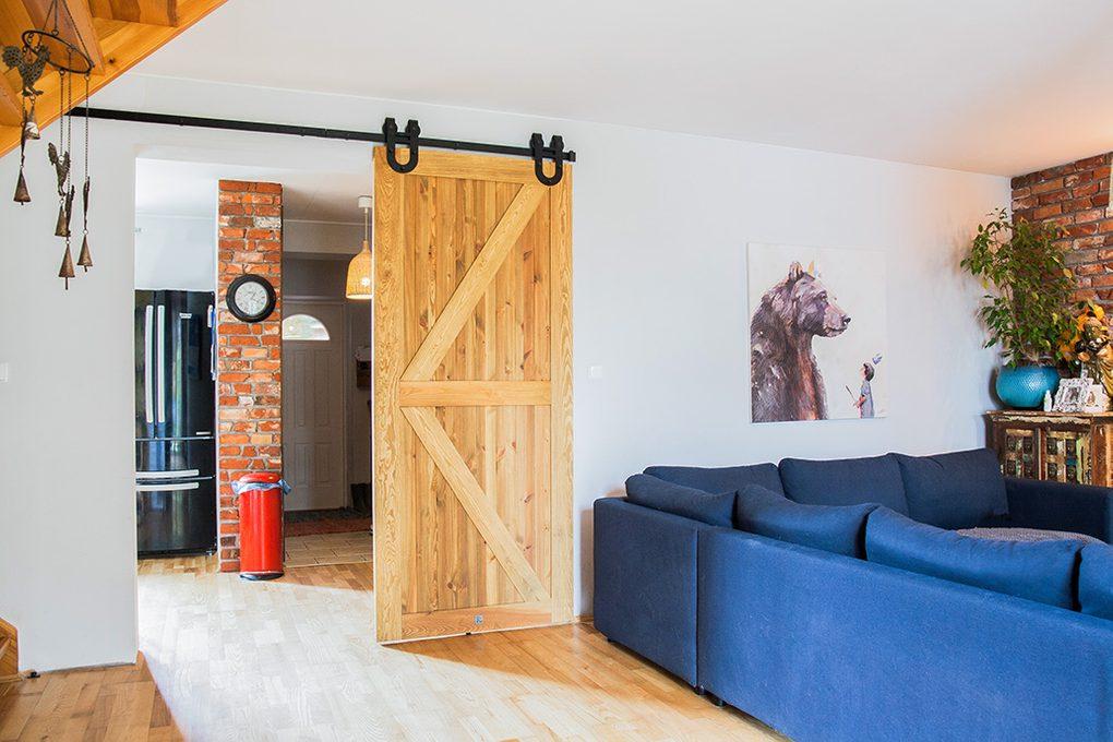 drzwi przesuwne drewanine szczotkowane, drzwi przesuwne barn door, drzwi przesuwne z podkową, drzwi drewaniane rustykalne, drzwi rustykalne, rustykalne dekoracje, cegła w salonie, niebieska sofa w salonie, między kuchnią a salonem