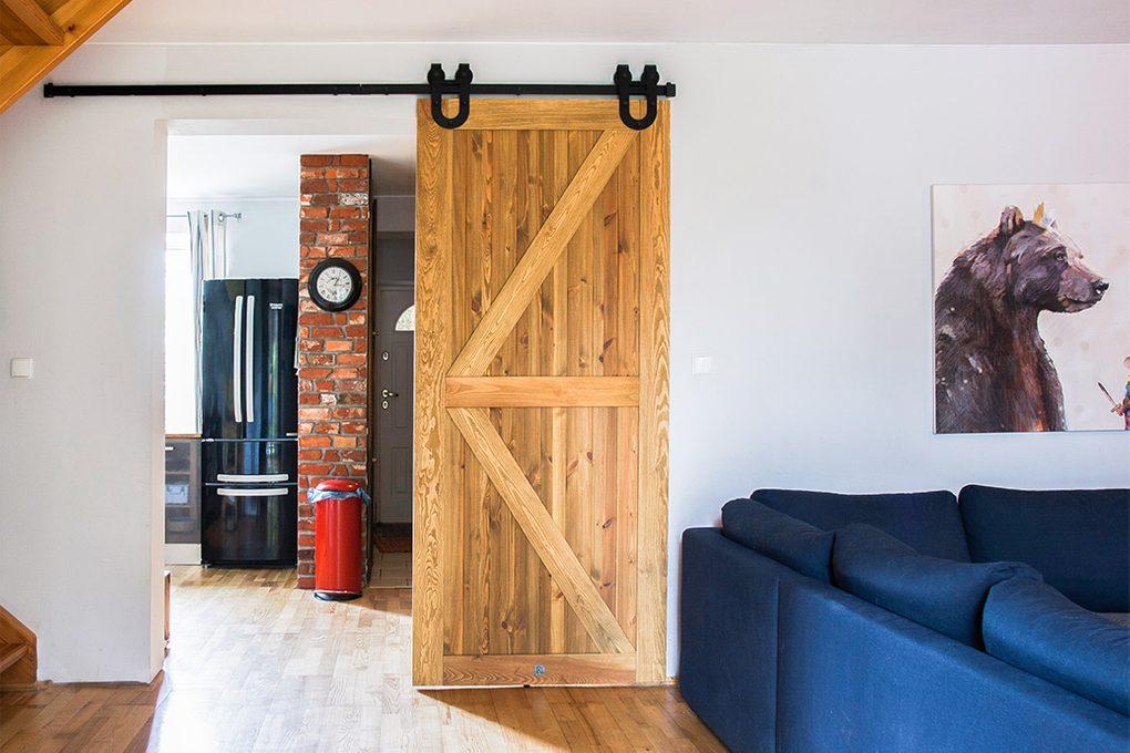drzwi przesuwne drewanine szczotkowane, drzwi przesuwne barn door, drzwi przesuwne z podkową, drzwi drewaniane rustykalne, drzwi rustykalne, wejście do salonu, wejście do kuchni, cegła na ścianie w kuchni