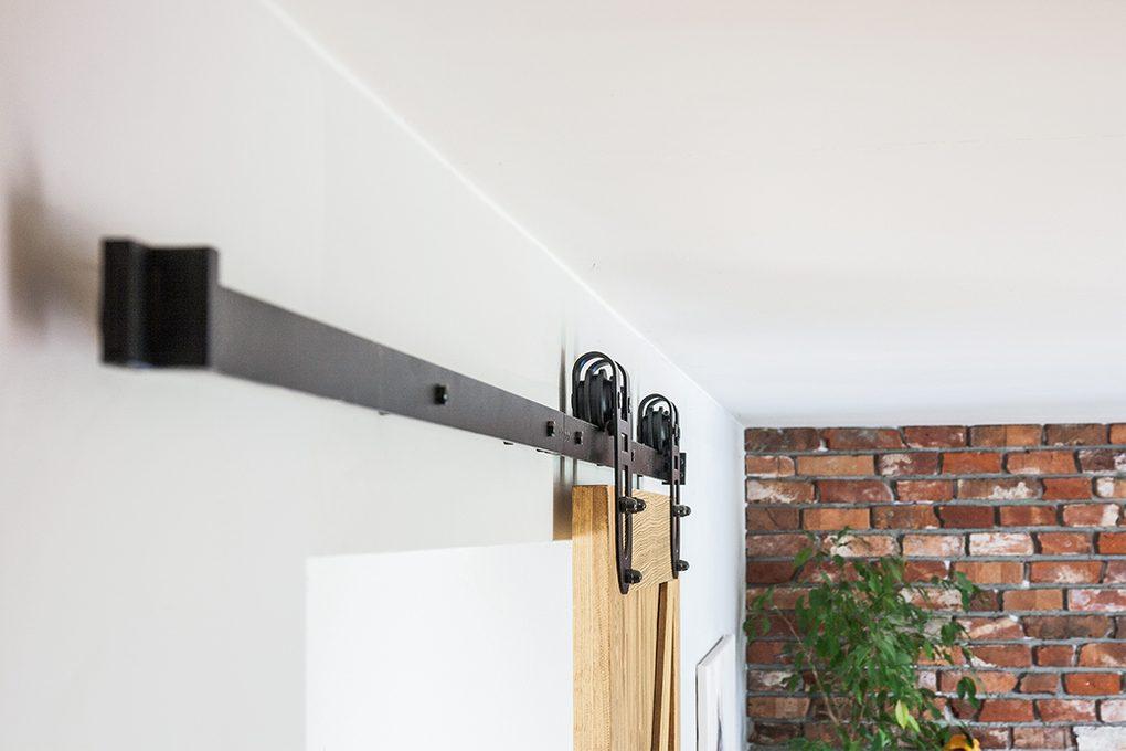 system przesuwny podkowa, prowadnica drzwi przesuwnych, wieszaki do drzwi przesuwnych, wieszaki podkowa, cegła na ścianie