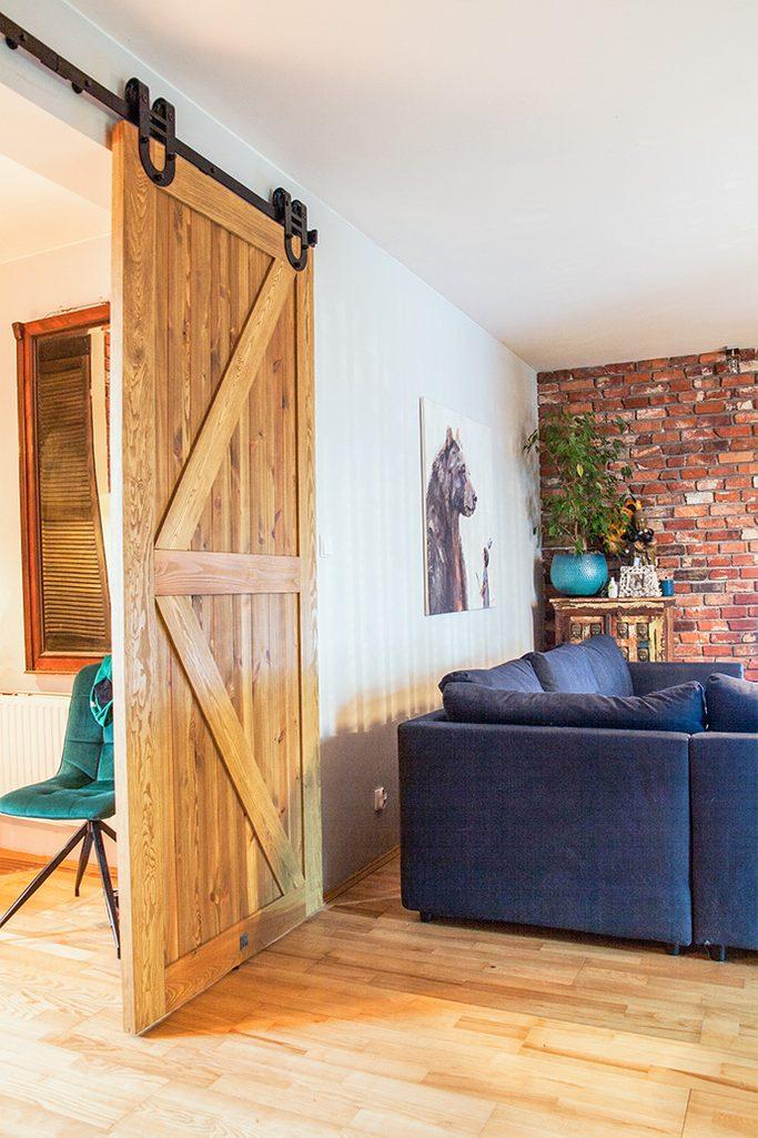 otwarta przestrzeń, wejście do salonu, drzwi przesuwne drewanine szczotkowane, drzwi przesuwne barn door, drzwi przesuwne z podkową, drzwi drewaniane rustykalne, drzwi rustykalne, niebieska sofa w salonie, cegła w salonie