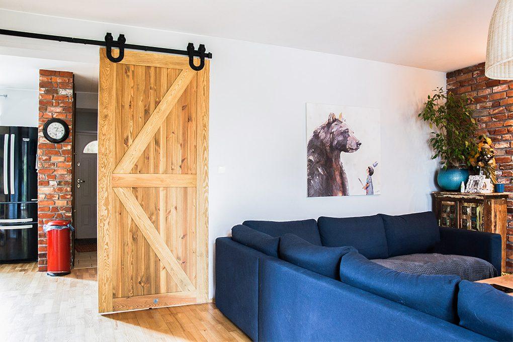 drzwi przesuwne drewniane szczotkowane, drzwi przesuwne z podkową, rustykalne wnętrze, cegła w salonie, niebieska sofa w salonie, przejście do salonu