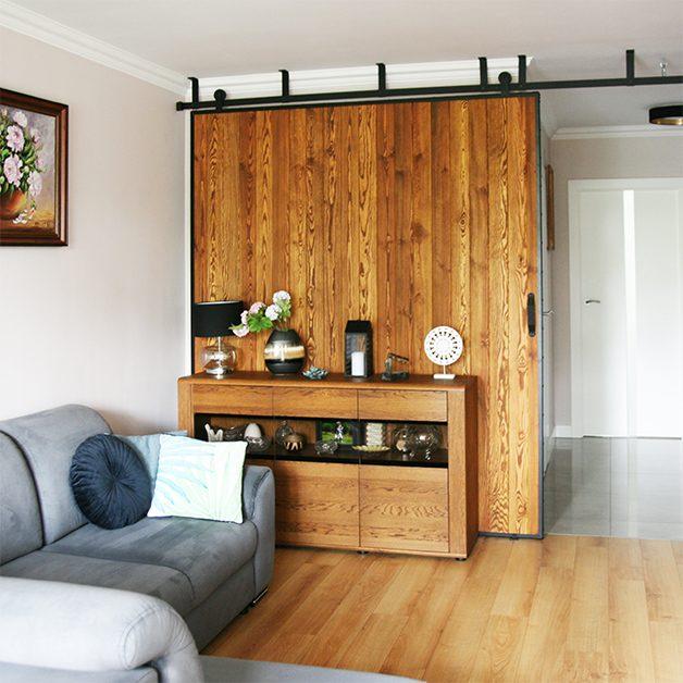 duże drzwi przesuwne, ściana przesuwna, jak oddzielić salon od reszty domu, drzwi przesuwne w bloku, drzwi przesuwne drewniane, drzwi przesuwne w metalowej ramie, aranżacja salonu w bloku, szara sofa w salonie, otwarty przedpokój w bloku
