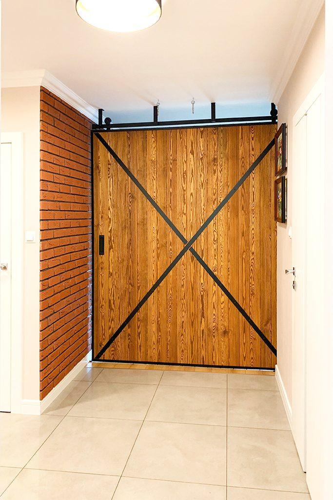 duże drzwi przesuwne, ściana przesuwna, jak oddzielić salon od reszty domu, drzwi przesuwne w bloku, drzwi przesuwne drewniane, drzwi przesuwne w metalowej ramie, cegła na ścianie w przedpokoju
