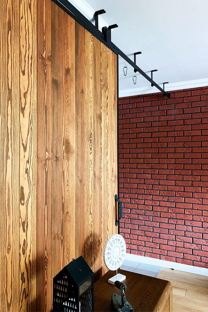 duże drzwi przesuwne, ściana przesuwna, jak oddzielić salon od reszty domu, drzwi przesuwne w bloku, drzwi przesuwne drewniane, drzwi przesuwne w metalowej ramie, cegła na ścianie w salonie, montaż sufitowy drzwi przesuwnych