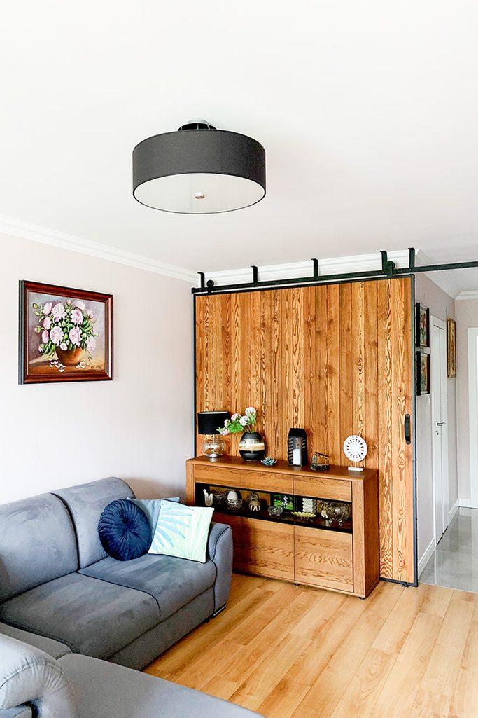 duże drzwi przesuwne, ściana przesuwna, jak oddzielić salon od reszty domu, drzwi przesuwne w bloku, drzwi przesuwne drewniane, drzwi przesuwne w metalowej ramie, aranżacja salonu w bloku, szara sofa w salonie
