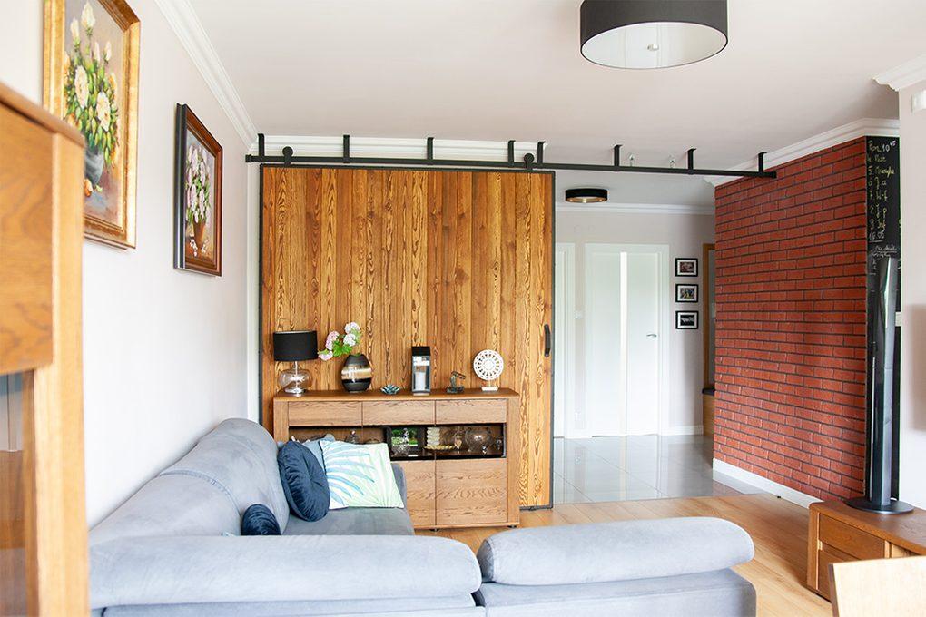 duże drzwi przesuwne, ściana przesuwna, jak oddzielić salon od reszty domu, drzwi przesuwne w bloku, drzwi przesuwne drewniane, drzwi przesuwne w metalowej ramie, cegła na ścianie, salon w bloku aranżacja
