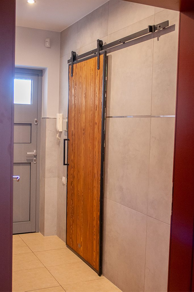 drzwi przesuwne w metalowej ramie, drzwi przesuwne drewaniane, drzwi przesuwne z litego drewna, drzwi przesuwne szczotkowane, drzwi do garderoby, drzwi przesuwne do garderoby