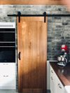 solidne drewniane drzwi przesuwne w kuchni, przesuwne drzwi do spiżarni, cegła na ścianie w kuchni