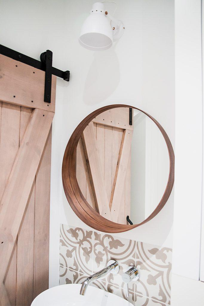 drzwi przesuwne rustykalne, drzwi przesuwne w łazience, drzwi w małej łazience, wejście do spiżarni, drewno w łazience, okrąge lustro w drewnianej ramie