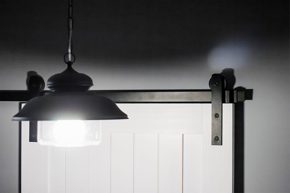 system przesuwny, białe drzwi przesuwne, szare ściany w przedpokoju, czarna lampa wisząca w przedpokoju