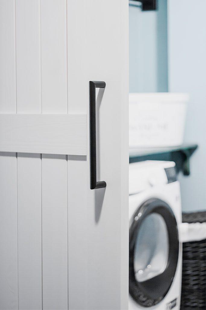 białe drzwi przesuwne, czarne dodatki, wejście do pralni, drzwi przesuwne do pralni, styl modern farmhouse