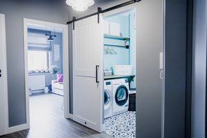 białe drzwi przesuwne, system drzwi przesuwnych, styl modern farmhouse, drzwi do pralni, drzwi przesuwne w przedpokoju, szare kolory, czarne elementy dekoracyjne