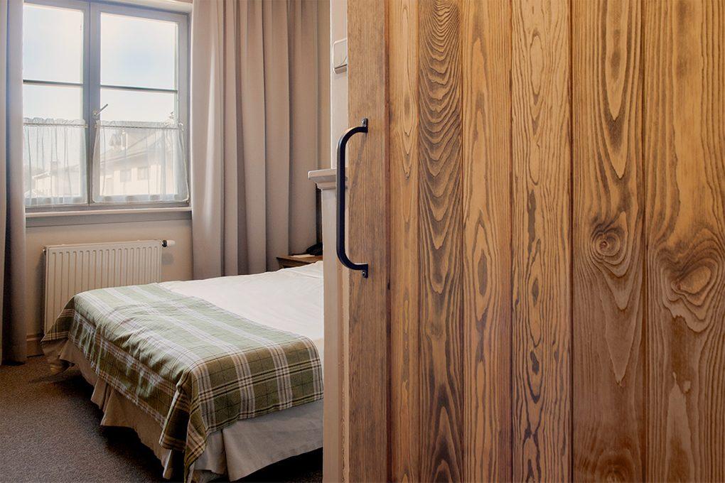 drzwi przesuwne w pokoju hotelowym, metalowy uchwyt do drzwi, rustykalne drzwi przesuwne