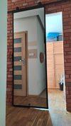 lustro w metalowej ramie, drzwi przesuwne, lustro przesuwne, ceglana ściana