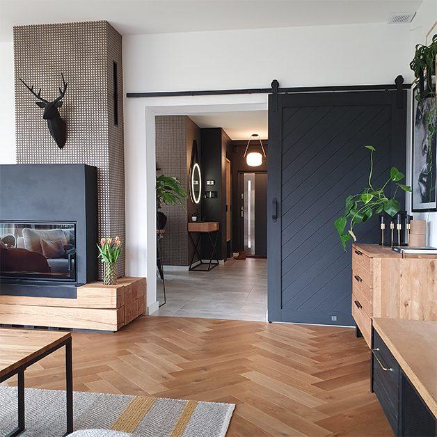 drewno i czerń, wejście do salonu z drzwiami przesuwnymi, drewniana komoda