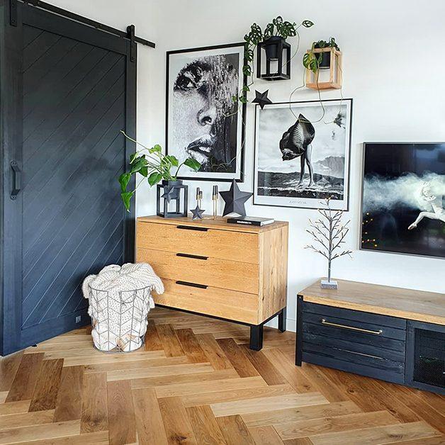 kolaż z grafikami na ścianie, czarne drzwi przesuwne, drewniana szafka z metalowymi nogami